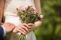Close-up dos noivos que guarda as mãos Wedding ao ar livre Recentemente casal - detalhes do casamento Apenas casado imagem de stock royalty free