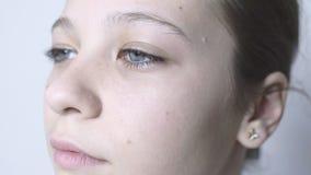 Close-up dos olhos azuis de uma moça Uma menina bonita com olhos grandes está estando no vento video estoque