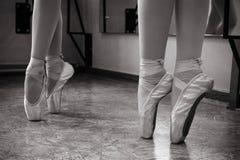Close-up dos pés da bailarina em sapatas do pointe no salão de dança Fotografia do vintage Close-up de uma bailarina no salão de  foto de stock