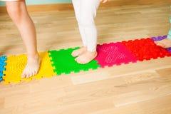 Close up dos pés da criança ao estar na esteira de massagem especial imagem de stock royalty free