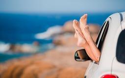 Close up dos pés da família que mostram da paisagem bonita do fundo da janela de carro Fotos de Stock Royalty Free