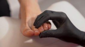Close up dos pés da mulher Limpeza da unha do pé usando o líquido de limpeza de prego do dedo do pé pelo especialista do pedicure video estoque