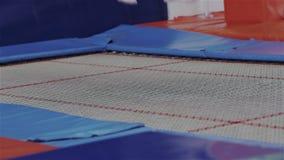 Close up dos pés da mulher quando ela que salta em um trampolim no gym Atividade de treinamento fêmea forte saudável dos desporti video estoque