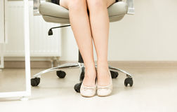 Close up dos pés das mulheres de negócios em planos do bailado sob a tabela do escritório Imagem de Stock Royalty Free