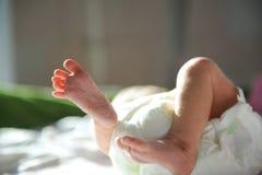Close up dos pés de recém-nascido na luz solar Foto de Stock