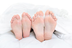 Close-up dos pés de um par na cama Fotos de Stock Royalty Free