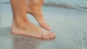 Close up dos pés desencapados do ` s da mulher que andam na praia na espuma do mar filme