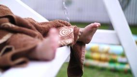 Close-up dos pés do ` s das crianças, uma menina de um ano pequena envolvida em uma toalha, balançando em um balanço no jardim, n video estoque