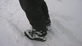 Close-up dos pés do ` s do homem que andam nas montanhas na neve Os pés do homem caem através da neve vídeos de arquivo