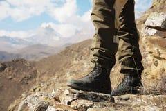 Close-up dos pés do ` s dos homens em caminhar botas na perspectiva das rochas e montanhas épicos caucasianos distantes das terra Imagem de Stock Royalty Free