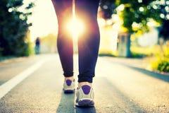 Close-up dos pés e das sapatas de atleta da mulher ao correr no parque Fotos de Stock