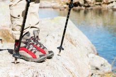 Close-up dos pés fêmeas em botas trekking com as varas para o nordic que anda na perspectiva das rochas e distante Fotografia de Stock