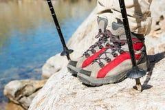 Close-up dos pés fêmeas em botas trekking com as varas para o nordic que anda na perspectiva das rochas e distante Imagem de Stock