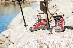 Close-up dos pés fêmeas em botas trekking com as varas para o nordic que anda na perspectiva das rochas e distante Imagens de Stock