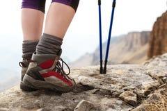 Close-up dos pés fêmeas em botas trekking com as varas para o nordic que anda na perspectiva das rochas e distante Imagens de Stock Royalty Free
