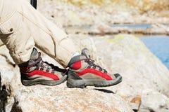 Close-up dos pés fêmeas em botas trekking na perspectiva das rochas e das terras caucasianos distantes Foto de Stock