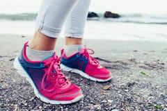 Close-up dos pés fêmeas nas sapatilhas e nas calças de brim na praia próximo imagem de stock royalty free