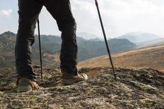 Close-up dos pés masculinos em botas trekking com as varas para o nordic que anda na perspectiva das rochas e distante Imagens de Stock