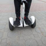 Close up dos pés masculinos em calças de brim à moda nas sapatilhas na moda em um giroscópio Passeios do indivíduo em um hoverboa imagens de stock