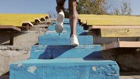 Close-up dos pés masculinos pretos na corrida crasso branca ao longo das etapas vídeos de arquivo