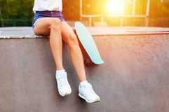 Close-up dos pés, menina com o patim no parque do patim, no por do sol imagens de stock