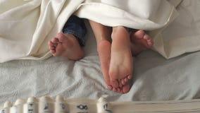 Close-up dos pés dos pares sob uma cobertura branca em uma cama branca filme
