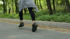 Close up dos pés que correm a menina através de um parque do outono video estoque