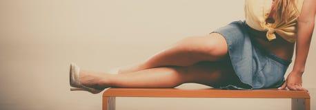 Close up dos pés 'sexy' da mulher nos saltos altos e na saia Imagem de Stock