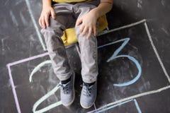 Close up dos p?s e das amarelinhas do ` s do rapaz pequeno tirado no asfalto Crian?a que joga amarelinha o jogo no campo de jogos fotos de stock