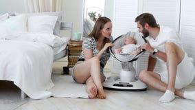 Close-up dos pais felizes que olham seu bebê pequeno dormir em casa em uma cadeira infantil de balanço em um apartamento branco E
