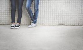 Close up dos pares de pés nas calças de brim Foto de Stock Royalty Free
