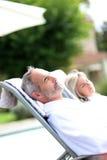 Close up dos pares que relaxam em cadeiras longas Imagem de Stock