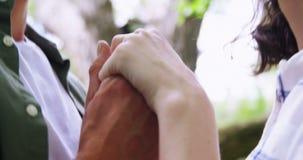 Close-up dos pares românticos que guardam as mãos no jardim filme