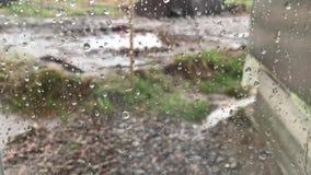 Close-up dos pingos de chuva na janela Uma gota da água rola sobre o vidro filme
