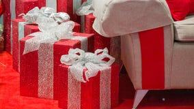 Close up dos presentes do Natal com a cadeira de Santa no direito do quadro foto de stock