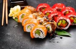 Close up dos rolos de sushi Alimento japonês no restaurante Role com o caviar dos salmões, da enguia, dos vegetais e dos peixes d Imagens de Stock Royalty Free