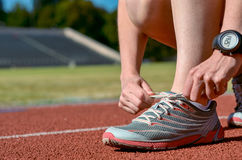 Close up dos tênis de corrida, atleta fêmea do corredor que amarra laços para treinar e movimentar-se na trilha do estádio, no es fotos de stock royalty free