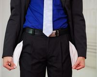 Close up of down part of a man wearing a suit holding his empty pockets consequence of being fired, in a blurred. Background Royalty Free Stock Images