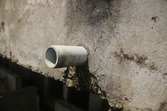 Close up of a drainage pipe sticking out a dirty grey wall royalty free stock photos
