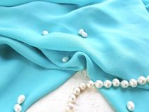 Close up drapped blue silk fabric with pearl beads on white background. royalty free stock photography