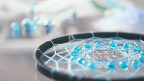 Close-up of Dreamcatcher black thread and turquoise beads. Lies on a glass background, turquoise beads around in slowmotion. Dreamcatcher - a product of the stock video footage