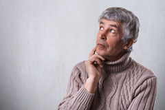A close-up of dreamy elderly male holding his hand under chin looking aside having thoughtful faraway expression. Mature man daydr Stock Photos