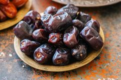 Close up of dried dates or kurma in a vintage plate. Close up of dried dates or kurma in a vintage plate on a rusty background Stock Photography