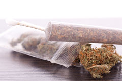 Close up of dried marijuana leaves and joint. Close up of dried marijuana leaves and tied end of marijuana joint with translucent rolling paper on white stock photo