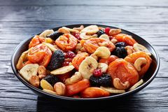 Close-up of dried organic Fruits and Nut Mix. Banana slices, apricots, raisins, prunes, cherries and cashew on a black plate on a wooden table, healthy eating royalty free stock images