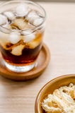 Close up in dried squid and cola in glass on wooden background.  Royalty Free Stock Photos