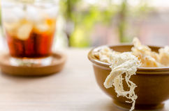 Close up in dried squid and cola in glass on wooden background.  Stock Image
