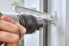 Close-up of drill that drills a hole in PVC window. Stock Image