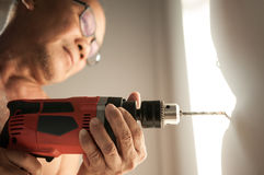 Close up drill, Old man using a drilling power tool. On white wall in his house, close up drill Royalty Free Stock Photos