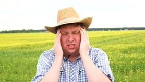 Close-up droevige jonge landbouwer met ongerust gemaakte beklemtoonde gezichtsuitdrukking Mens in cowboyhoed met hoofdpijn stock video